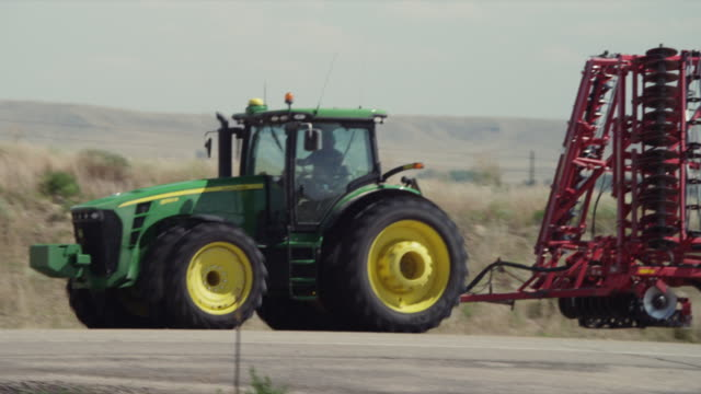 A John Deere farm tractor w/ disc driving down a highway