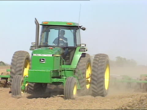John Deere large-frame tractor w/ tilling attachment moving
