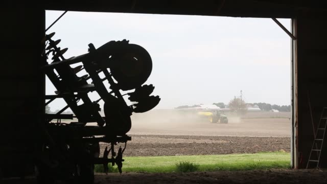 john deere tractor pulls a planter planting non-gmo seed corn in malden, illinois, u.s. on tuesday, may 17, 2017. shots: view from behind of planter... - modificazione genetica video stock e b–roll