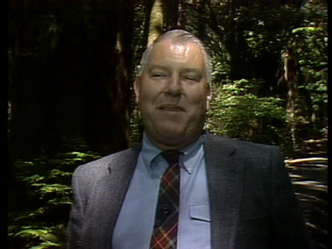 john dewitt of the save the redwoods league says the natural enemy of the redwoods is man and his demand for lumber which has been insatiable - 木を抱く点の映像素材/bロール