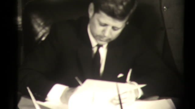jfk john f kennedy signs appointment of johnson in the white house oval office politicians gather behind desk washington dc politics governement - office politics stock videos & royalty-free footage