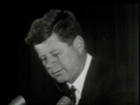 vídeos de stock, filmes e b-roll de john f kennedy standing at podium with microphone as cameras flash / united states - desaparecer gradualmente