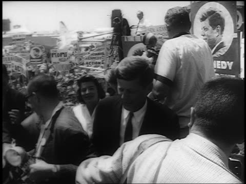 John F Kennedy walking through crowd outdoors at Democratic National Convention