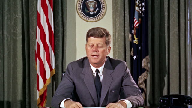 ms jfk john fitzgerald kennedy sitting at desk and speaking, presidential seal in background / washington d.c., united states - politik stock-videos und b-roll-filmmaterial
