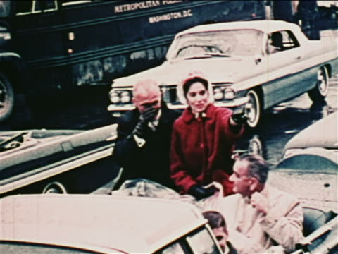 vídeos y material grabado en eventos de stock de john glenn + wife pointing + riding in convertible with lyndon johnson in parade / newsreel - pareja de mediana edad