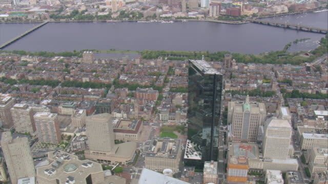 aerial john hancockbuilding rising above the city along the charles river waterfront / boston, massachusetts - river charles stock videos & royalty-free footage