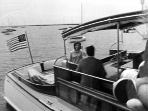 stockvideo's en b-roll-footage met john jacqueline kennedy on cabin cruiser pulling away from dock / hyannis port - jacqueline kennedy