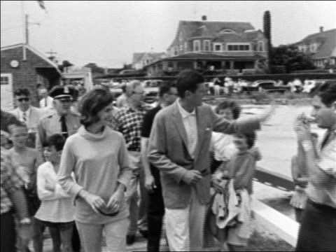 stockvideo's en b-roll-footage met john jacqueline kennedy walking on pier followed by people / hyannis port - jacqueline kennedy