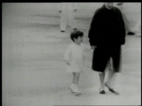 John Kennedy Jr being led away by woman and crying and looking back / United States