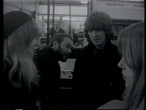 john lennon and george harrison with wife pattie boyd prepare to leave for india at airport / george harrison followed by his wife pattie and her... - ビートルズ点の映像素材/bロール