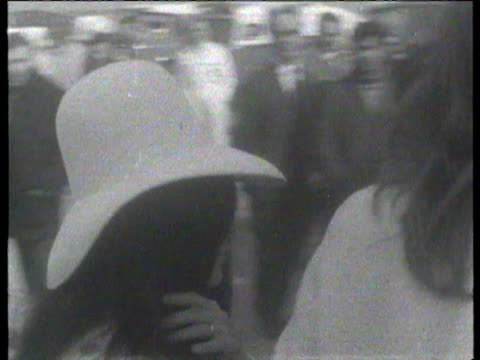 John Lennon and new wife Yoko Ono walk down steps of plane / Pair stop to pose for media / John and Yoko interviewed about their bedin 'if we make...