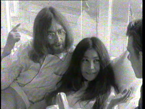 john lennon in bed with wife yoko ono during their honeymoon 'bedin' at the amsterdam hilton hotel to promote peace / 'we're going to stay in bed for... - frieden stock-videos und b-roll-filmmaterial