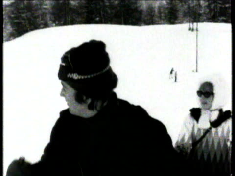 john lennon in ski gear skiing down ski slopes with woman / john falls over in snow john lennon skiing in st moritz on january 29 1965 in st moritz... - スキーウェア点の映像素材/bロール