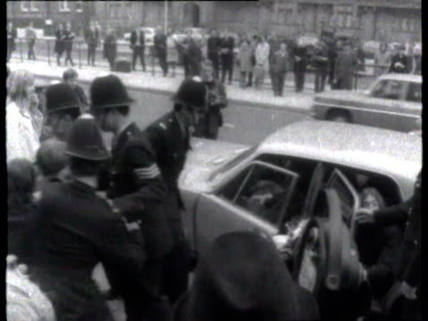 John Lennon of The Beatles arrives at court on drug charges gets out of car with girlfriend Yoko Ono / car surrounded by police officers and press...