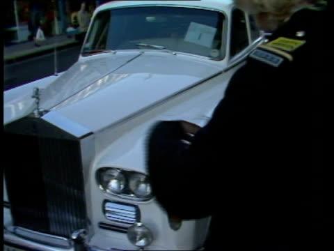 vídeos de stock, filmes e b-roll de john lennon's rolls royce song over sof 'lovely rita meter maid' bv female traffic warden marking down rolls royce pan rl la warden takes... - rolls royce