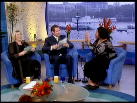 cleared of sexual assault allegations claim; lib england: london: int cms fern britton and john leslie on the set of 'this morning' lib cms newspaper... - in front of点の映像素材/bロール