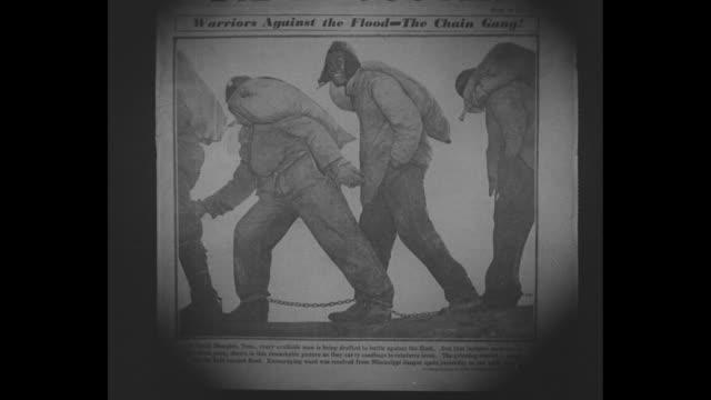 john lindsay, associated press photographer, with camera / newspaper article with chain gang carrying sandbags / actual chain gang men in raincoats... - レインコート点の映像素材/bロール