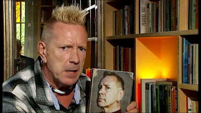 john lydon interview; england: int john lydon picks up his autobiography and sot - i look at it like 'cor that man's a bit hard and severe' but at... - biografia video stock e b–roll