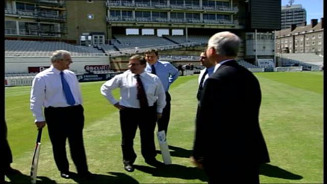 london the oval cricket ground ext john major graham thorpe walking along on pitch / major thorpe with others line up holding bats as pose for press... - graham thorpe stock videos and b-roll footage