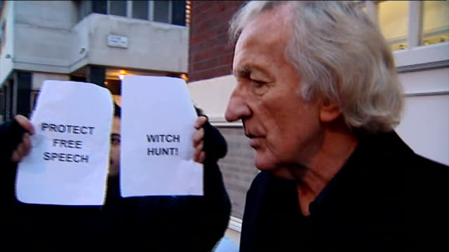 john pilger outside court with press crowded around and pilger with 'protect free speech' and 'witch hunt' signs held up behind as speaks to press... - pilger stock-videos und b-roll-filmmaterial
