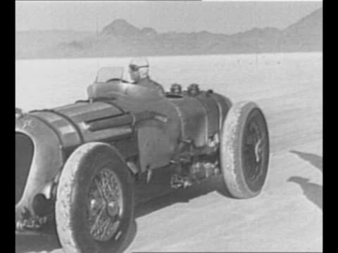 john rhodes cobb drives race car in reverse on utah salt flats as crew runs alongside car has british flag emblem on chassis / car stands ready to... - bonneville salt flats stock videos and b-roll footage