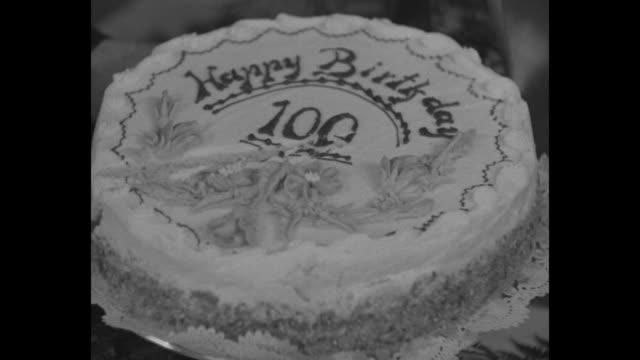 vídeos de stock e filmes b-roll de john soda ash johnny horan cuts into birthday cake happy birthday 100 / cu cake / sot horan i'm hale and hearty 83 years of service with the... - centenário