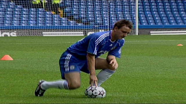 john terry appointed as new england captain; england: london: ext john terry crouched on pitch with ball posing for press - football strip stock videos & royalty-free footage