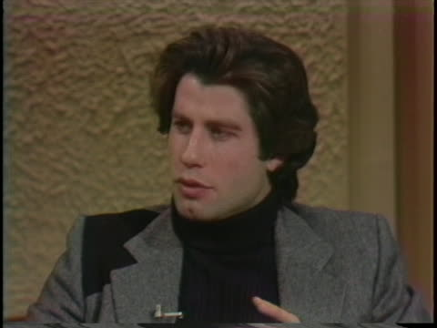 john travolta is asked to compare his role in the movie grease to his role in the movie, saturday night fever. he says grease is a light piece,... - music or celebrities or fashion or film industry or film premiere or youth culture or novelty item or vacations点の映像素材/bロール
