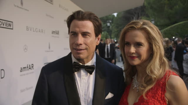 vídeos y material grabado en eventos de stock de interview john travolta kelly preston on being at amfar at amfar red carpet at hotel du capedenroc on may 22 2014 in cap d'antibes france - kelly preston