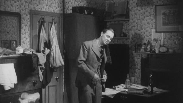 vídeos de stock, filmes e b-roll de 1943 montage john treating his new suit very poorly, taking it off and throwing the bits around the bedroom / united kingdom - balançando