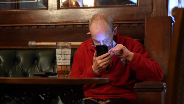 john uses his mobile phone while sitting with a pint of beer in the goat major pub on october 20 in cardiff, wales. wales will go into a national... - beer alcohol stock videos & royalty-free footage