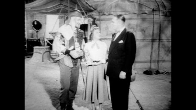 john wayne and june allyson receive awards from a national women's magazine while working on film set / actors examine individual awards / smiling... - anno 1954 video stock e b–roll