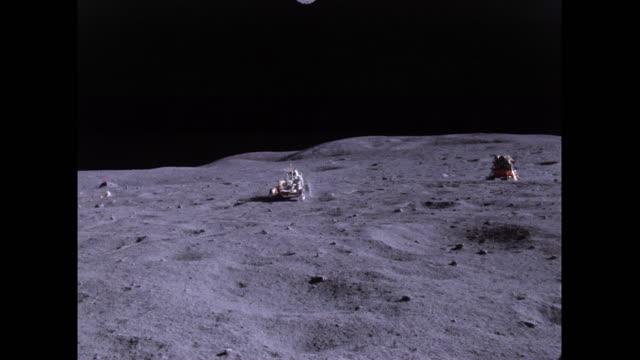 vídeos de stock, filmes e b-roll de john young is driving in the lrv, filmed by charles duke. - missão espacial