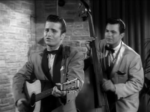 "b/w 1956 johnny burnette + bassist performing  ""lonesome train"" on small stage / feature - klassischer rock and roll stock-videos und b-roll-filmmaterial"
