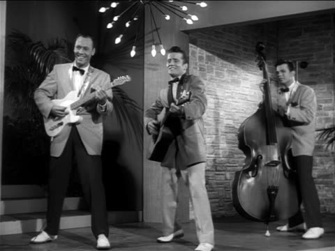 "b/w 1956 johnny burnette + his rockabilly trio performing  ""lonesome train"" on small stage / feature - pop musician stock videos & royalty-free footage"