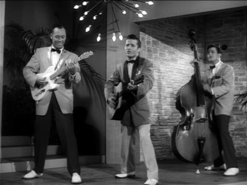 "b/w 1956 johnny burnette + his rockabilly trio performing  ""lonesome train"" on small stage / feature - klassischer rock and roll stock-videos und b-roll-filmmaterial"