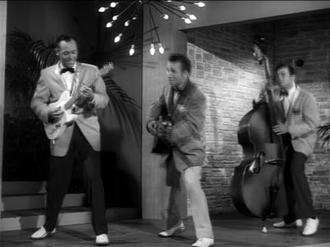"vídeos de stock e filmes b-roll de b/w 1956 johnny burnette + his rockabilly trio performing  ""lonesome train"" on small stage / feature - 1956"