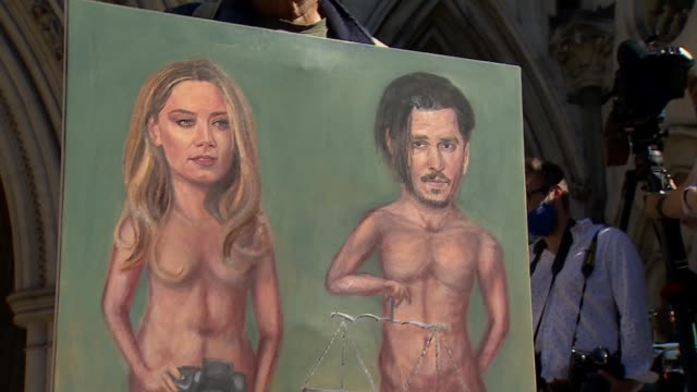 johnny depp arrival england london royal courts of justice ext man standing outside court holding drawn court case themed mural of amber heard and... - news not politics stock videos & royalty-free footage