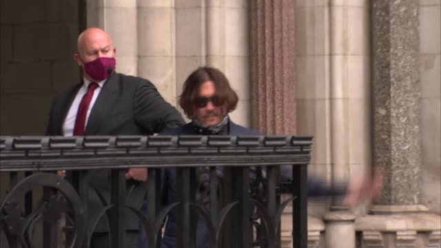 johnny depp libel trial: johnny depp arrives; england: london: ext johnny depp along from car and waving to media before into court / - 文書による名誉棄損点の映像素材/bロール