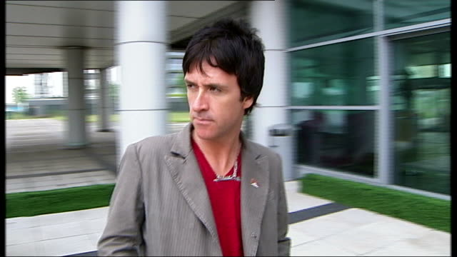 johnny marr interview england overlay the smith this charming man** johnny marr stands by canalside building - ジョニー マー点の映像素材/bロール