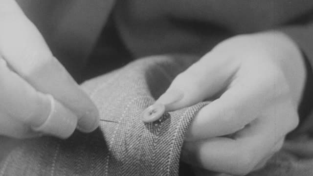 vidéos et rushes de 1943 montage john's wife mending, cleaning, shaking, and ironing his suit / united kingdom - costume