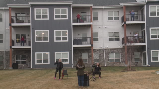 johnston, ia, u.s. - senior residents on johnston senior complex exercising on balconies on wednesday, march 25, 2020. - instructor stock videos & royalty-free footage