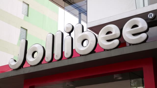 stockvideo's en b-roll-footage met a jollibee foods corp restaurant stands in manila philippines on friday nov 20 a security guard opens doors for customers exiting a jollibee foods... - filipijnse etniciteit