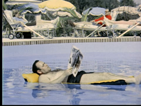 jonathan winters in bathing suit lying on raft in swimming pool reading newspaper. dips fingers in water to turn pages. zoom into magazine article on... - zeitschrift stock-videos und b-roll-filmmaterial