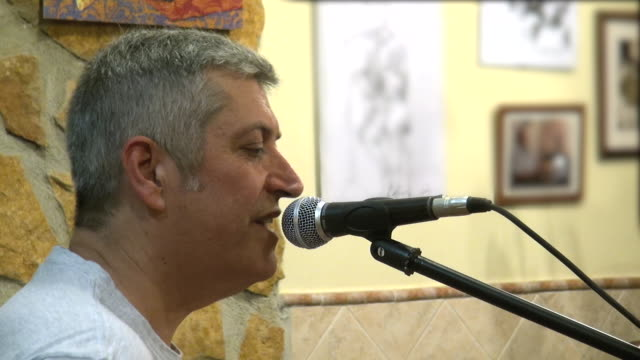 jose luis palomares rodriguez playing spanish folk rock music on guitar in a small town in spain - moderne rockmusik stock-videos und b-roll-filmmaterial