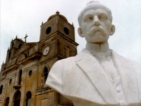 cu, jose marti bust with church in background, nuevitas, cuba  - male likeness stock videos & royalty-free footage
