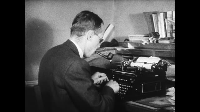 Joseph Furnas typing on typewriter smoking pipe looking at page in typewriter