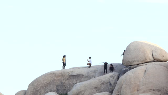 joshua tree men and women on top of large boulders slowly climbing down, - joshua tree national park stock videos & royalty-free footage