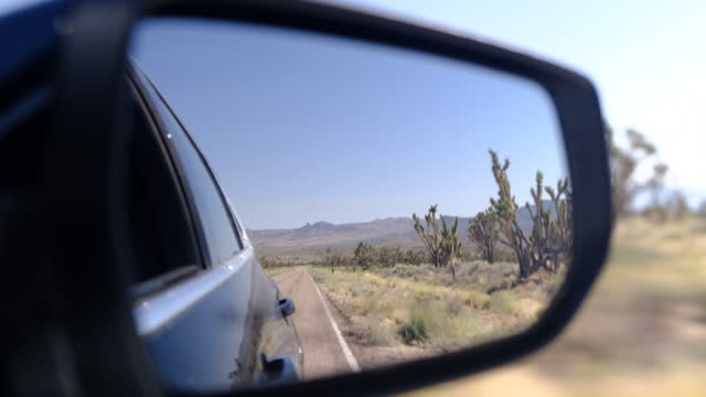 joshua tree national park, movement on an empty road going into the distance to red mountain rocks in the canyon landscape in the dry desert. the road with the black asphalt and the orange markings. slow motion, sunny day - joshua tree national park stock videos & royalty-free footage