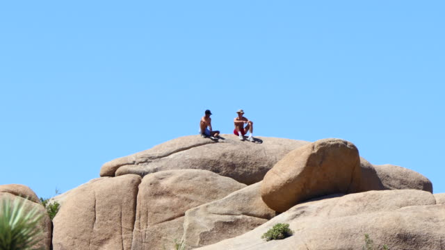 vidéos et rushes de joshua tree national park, southern california, two young men sitting and talking on top of large boulders, slight zoom out, - exposé aux intempéries